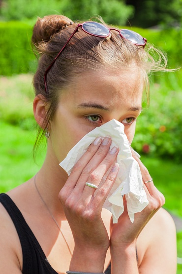 Teenage girl with hay fever and handkerchief